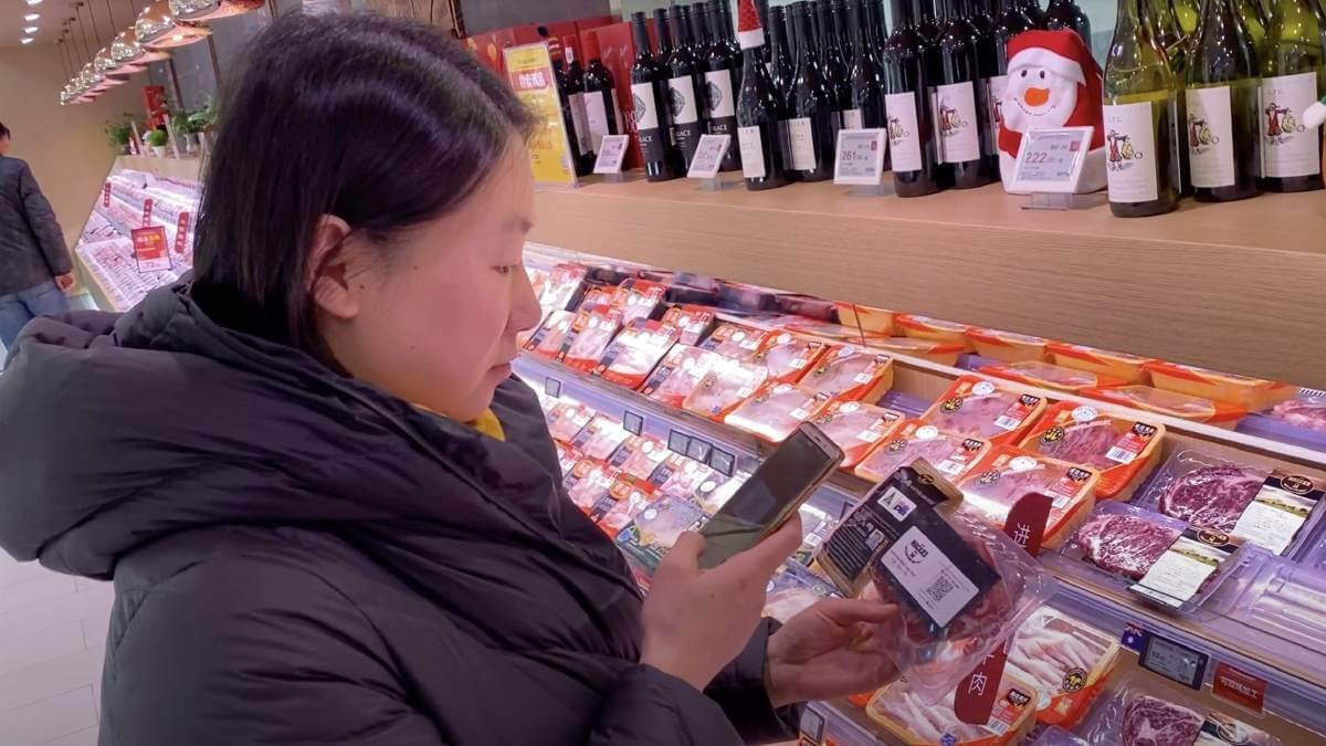woman checks blockchain tag on beef